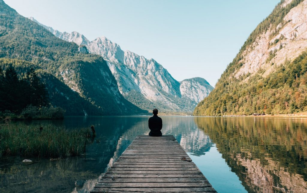 A person sitting on the end of a small pier, surrounded by a lake between two mountains