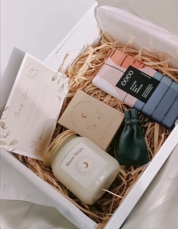 naturally elevate self-care box featuring a candle, chocolate bar, affirmation cards and a choice of three crystal pendants